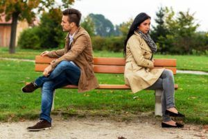 a young couple sitting on a park bench and make war