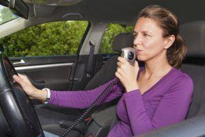 Woman in car blowing into breathalyzer