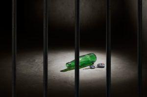 empty beer bottle and car key behind bars, don't drink and drive concept